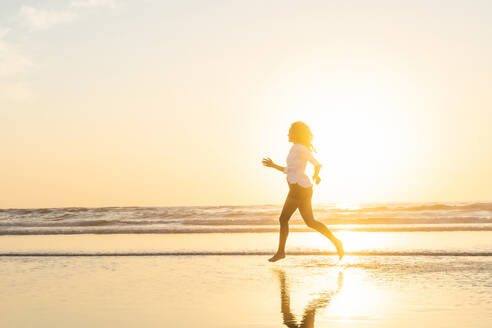 In silhouette of woman running in sea during sunset - SBOF02337