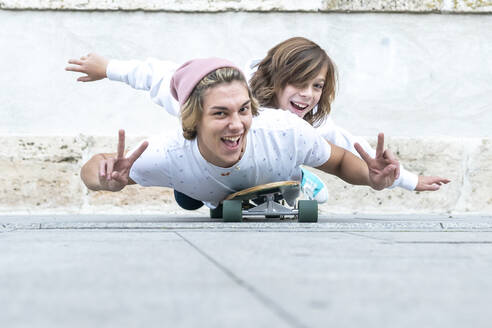 Smiling friends gesturing peace sign while lying on skateboard against footpath - GGGF00674