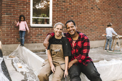 Portrait of confident couple sitting on concrete while children playing in background against house - MASF21124