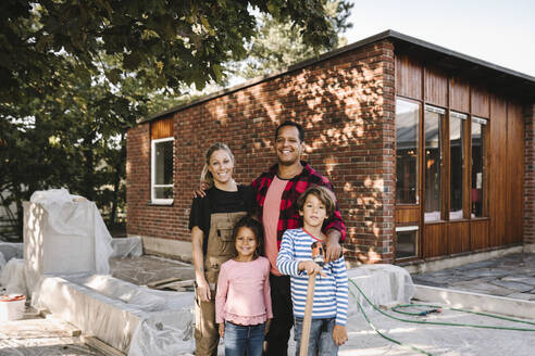 Portrait of smiling couple with children standing against house - MASF21142