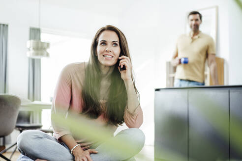 Smiling mature woman on phone call with man in background at home - JOSEF02726