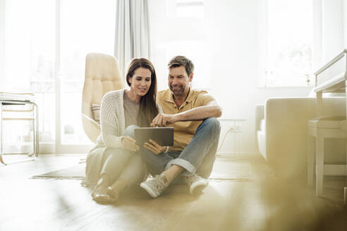Smiling mature couple using digital tablet together while sitting on floor at home - JOSEF02756