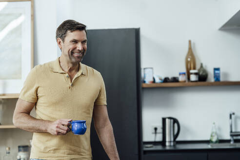 Happy mature man holding coffee cup while standing in kitchen at home - JOSEF02786