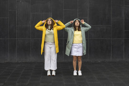 Young women wearing raincoats looking up while standing against black wall - AXHF00013