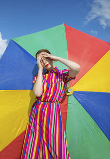 Carefree woman against colorful beach umbrella on sunny day - AXHF00022