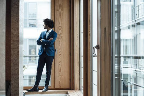 Thoughtful male entrepreneur standing with arms crossed looking away through window at office - JOSEF02849