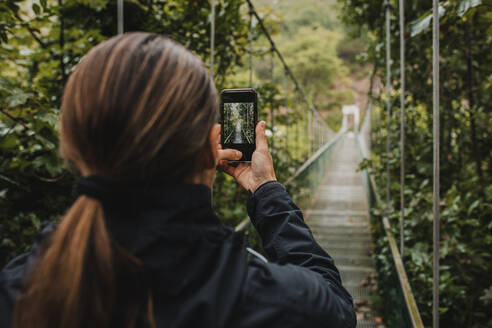 Woman photographing with mobile phone on suspension bridge in forest - DMGF00428