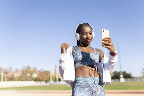 Sportswoman listening music while taking selfie through smart phone against clear sky - JCCMF00515