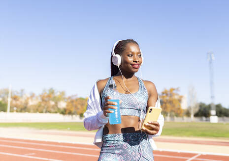 Smiling sportswoman looking away while listening music holding energy drink and smart phone against clear sky - JCCMF00518