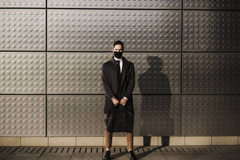 Young businessman wearing protective face mask carrying briefcase while standing against silver colored wall - EBBF01991