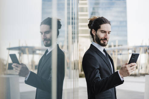 Young entrepreneur using mobile phone while standing by glass wall - EBBF02012