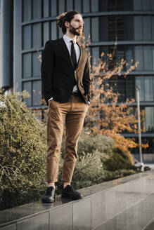 Young businessman with hands in pockets looking away while standing on retaining wall - EBBF02018