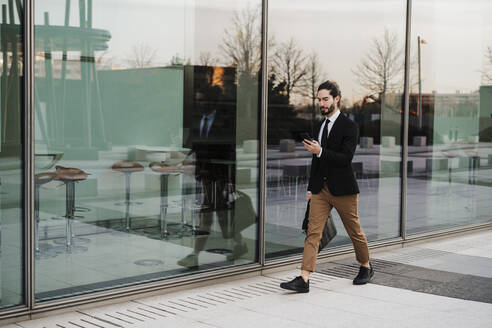 Young businessman using mobile phone while walking on footpath - EBBF02030