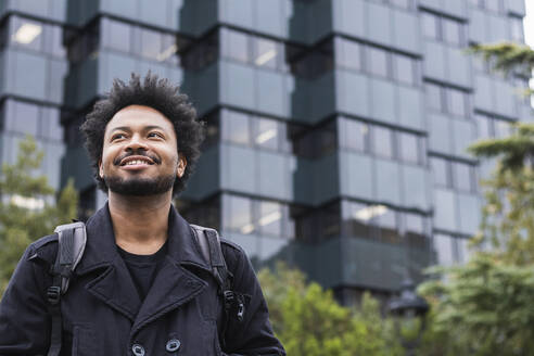 Smiling man with afro hair looking away while standing against modern building - PNAF00453