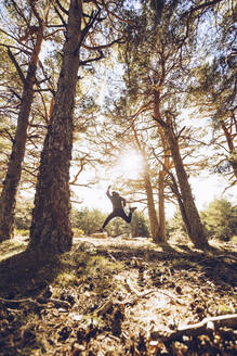 Cheerful young man jumping on land in forest - RSGF00474