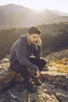 Young man talking over smart phone while sitting on mountain - RSGF00495