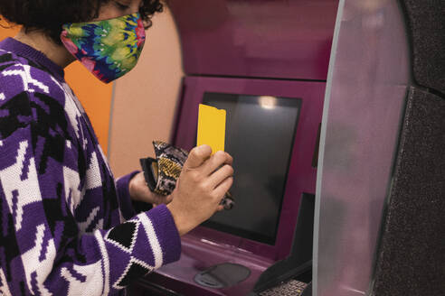 Young woman wearing face mask using credit card at ATM - PNAF00559