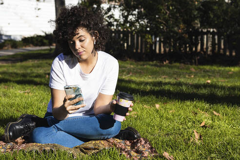 Young woman with disposable coffee cup using mobile phone while sitting at park - PNAF00565