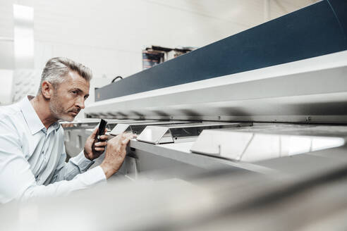 Mature inspector examining machine while standing at industry - JOSEF03053