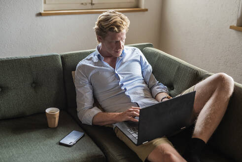 Male freelancer working over laptop while sitting on couch at home - MEF00083