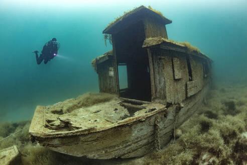 Scuba diver swimming toward shipwreck sunken in Lake Atter - YRF00263