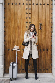 Smiling mid adult woman with wheeled luggage using mobile phone against wood door - EBBF02079