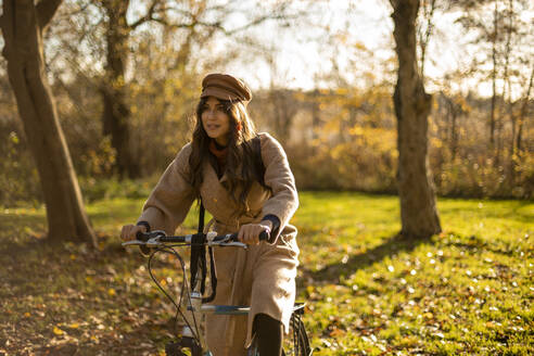 Fashionable woman sitting on bicycle in public park - AXHF00026