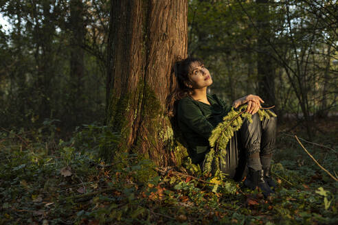 Beautiful woman with branch day dreaming while leaning on tree trunk in public park - AXHF00029