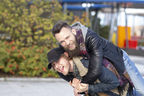 Playful mid adult man piggybacking boyfriend while standing in city - JCCMF00675