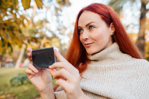 Close-up of beautiful woman photographing with mobile phone in park - MRRF00772