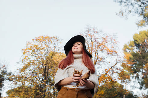 Thoughtful woman wearing hat holding autumn leaves while standing against clear sky in park - MRRF00775