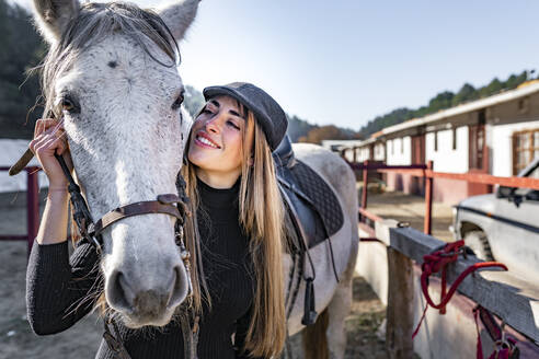 Smiling woman with horse in paddock - GGGF00753