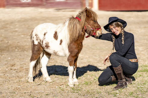Portrait of smiling woman with pony in paddock - GGGF00780