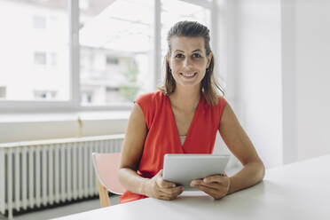 Portrait of businesswoman with digital tablet sitting in office - GUSF05017