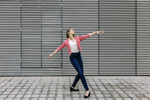 Spain, Barcelona, Young businesswoman dancing in city - XLGF00956