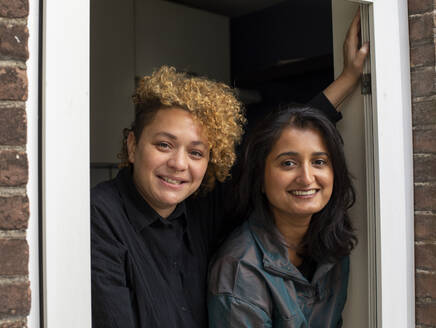 Portrait of happy lesbian couple standing together in front of window - AXHF00066