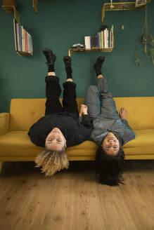 Portrait of lesbian couple lying upside down on sofa - AXHF00075