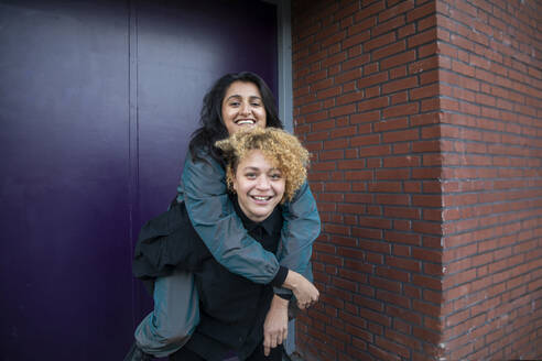 Young woman piggybacking girlfriend in front of building entrance - AXHF00093