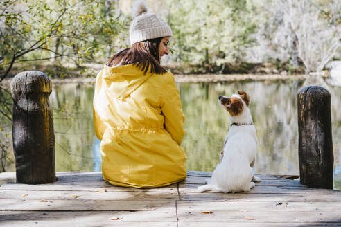 Woman with dog sitting on pier by lake in Autumn - EBBF02103