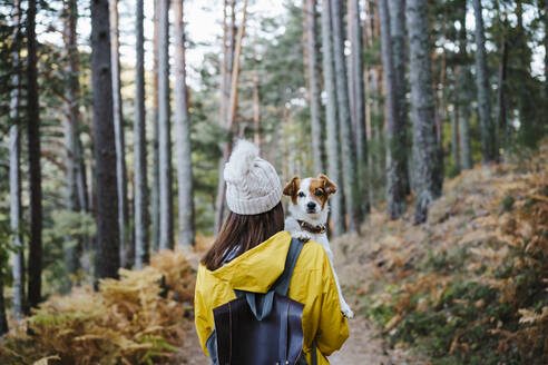 Woman carrying dog in forest - EBBF02112