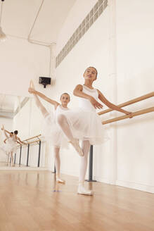 Low angle of charming teenage ballerinas in pointe shoes stretching legs near ballet barre in dance hall - ADSF19764