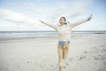 Portrait of young woman running on sandy beach with raised arms - UUF22536