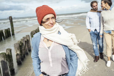 Portrait of young woman wearing scarf and knit hat standing on beach - UUF22545