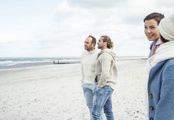 Group of adult friends standing and talking on coastal beach - UUF22551