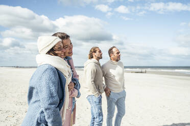 Group of adult friends standing and talking on coastal beach - UUF22554