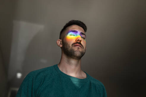 man with rainbow light reflections hitting his face indoors - spain, andalucia, almeria - MIMFF00394