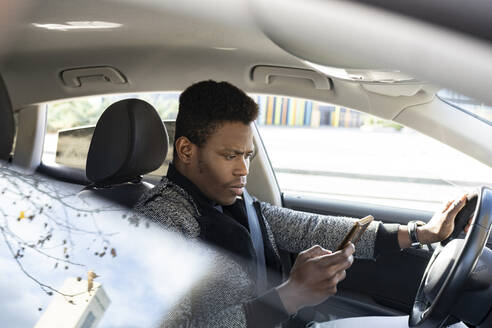 Young man driving car and using smartphone - JCCMF00792