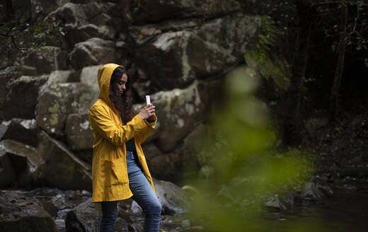 Woman wearing yellow raincoat photographing while smart phone in forest - KBF00653