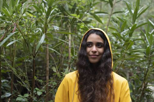Young woman wearing yellow raincoat contemplating while standing against plants in forest - KBF00668