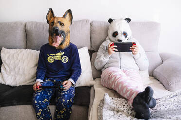 Siblings wearing animal costumes playing handheld video game while sitting on sofa at home - JCMF01788